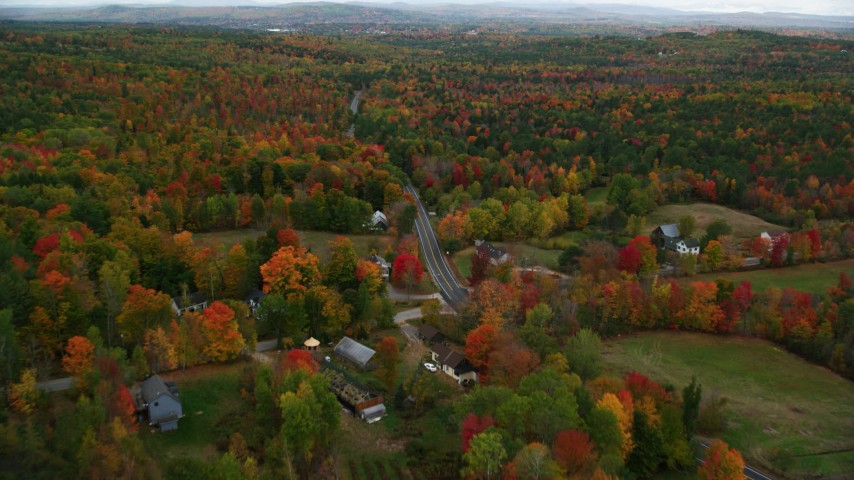 6K stock footage aerial video flying over colorful forest, rural homes, Buckfield Road, autumn, Paris, Maine Aerial Stock Footage | AX150_075