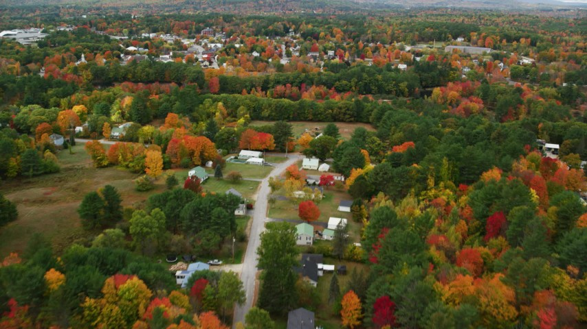 6K stock footage aerial video flying over rural homes, colorful trees, tilt up to reveal small town, autumn, Paris, Maine Aerial Stock Footage | AX150_082