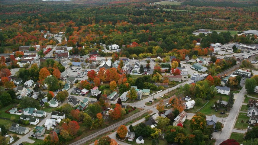 6K stock footage aerial video orbiting brightly colored foliage throughout small rural town, autumn, Paris, Maine Aerial Stock Footage | AX150_085