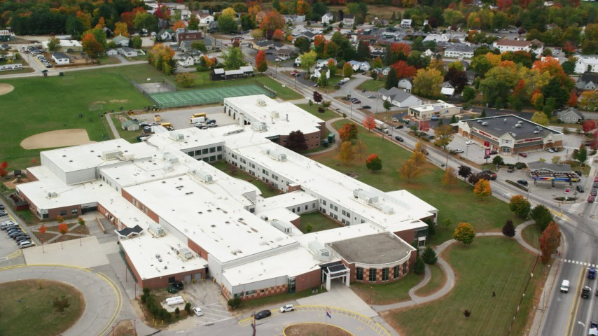 6K stock footage aerial video approaching Oxford Hills Comprehensive High School, tilt down, autumn, Paris, Maine Aerial Stock Footage | AX150_095