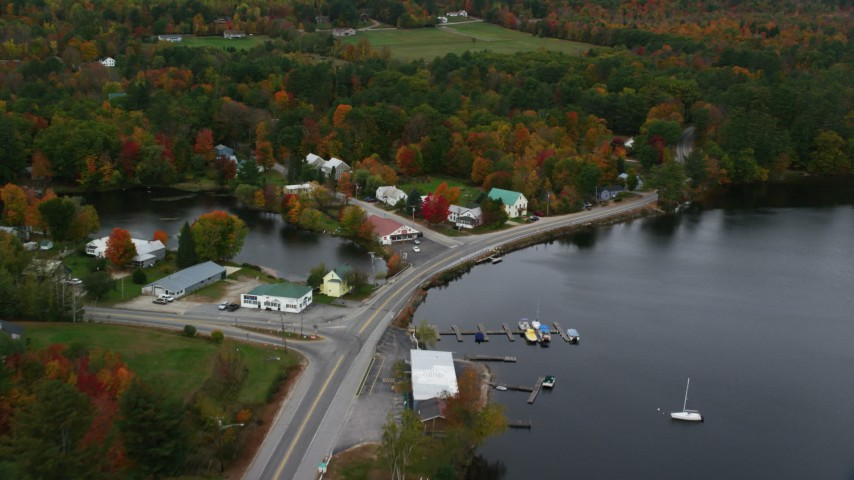 6K stock footage aerial video tilting down on waterfront rural homes, store in autumn, Lake Pennesseewassee, Norway, Maine Aerial Stock Footage | AX150_101