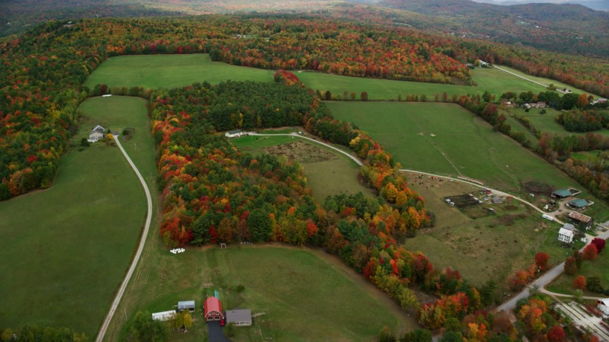 6K stock footage aerial video flying by small farms, green fields, colorful trees in autumn, Norway, Maine Aerial Stock Footage | AX150_105