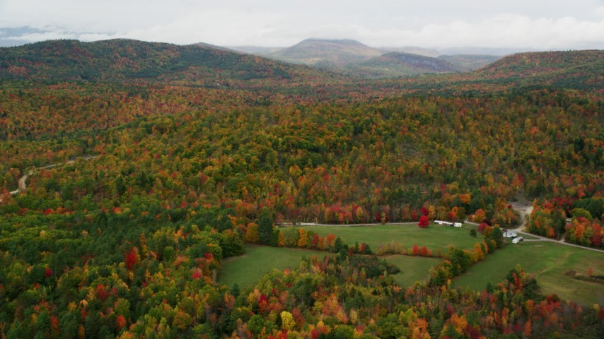6K stock footage aerial video flying over a brightly colored forest in autumn, overcast, Waterford, Maine Aerial Stock Footage | AX150_114
