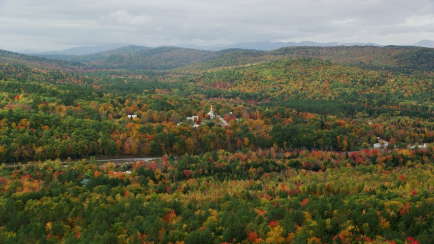 6K stock footage aerial video approaching small rural town, brightly colored forest, autumn, Waterford, Maine Aerial Stock Footage | AX150_116