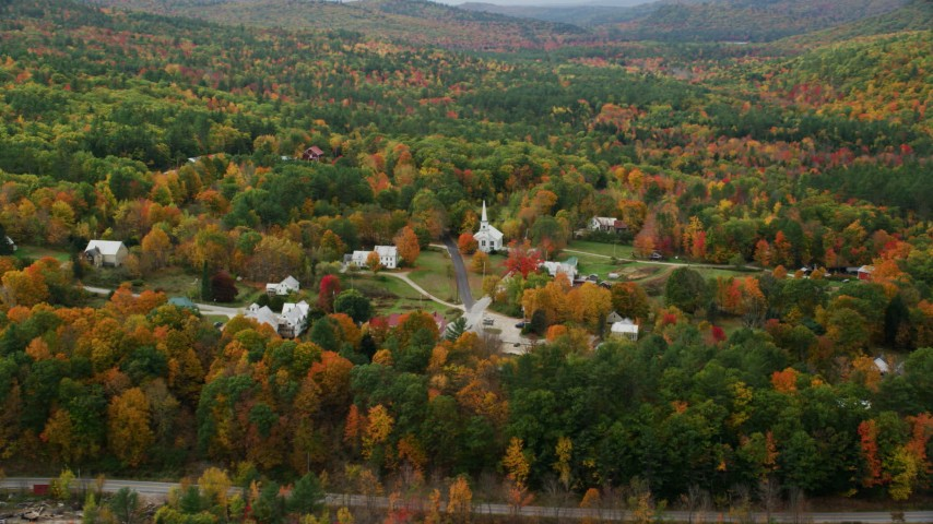 6K aerial video orbiting small rural town, dense forest in autumn, Waterford, Maine Aerial Stock Footage AX150_117