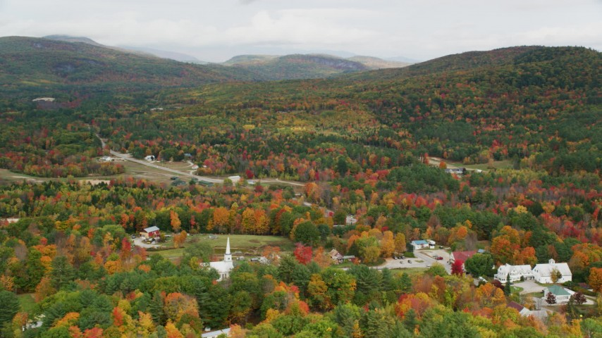 6K stock footage aerial video orbiting small rural town, dense forest, hills, autumn, overcast, Waterford, Maine Aerial Stock Footage | AX150_121