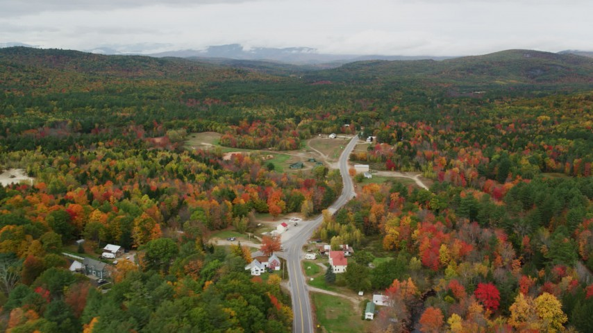 6K stock footage aerial video flying by small rural town, Valley Road, autumn, overcast, Waterford, Maine Aerial Stock Footage | AX150_123