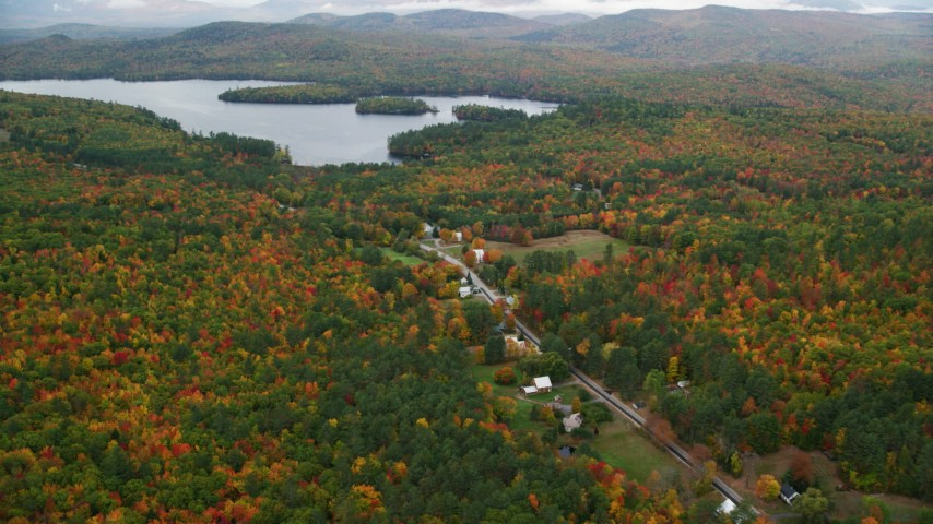 6K aerial video flying over forest, approach Cezar Lake, tilt down on rural homes, autumn, overcast, Lovell, Maine Aerial Stock Footage | AX150_137