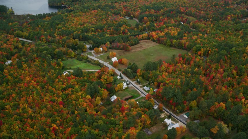 6K aerial video of a bird's eye view of rural homes, Maine Street, brightly colored trees, autumn, Lovell, Maine Aerial Stock Footage | AX150_138