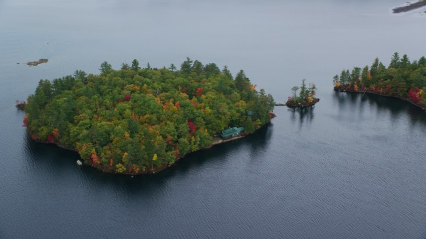6K aerial video flying by Sheep Island waterfront home, colorful trees, Kezar Lake, autumn, Lovell, Maine Aerial Stock Footage | AX150_139