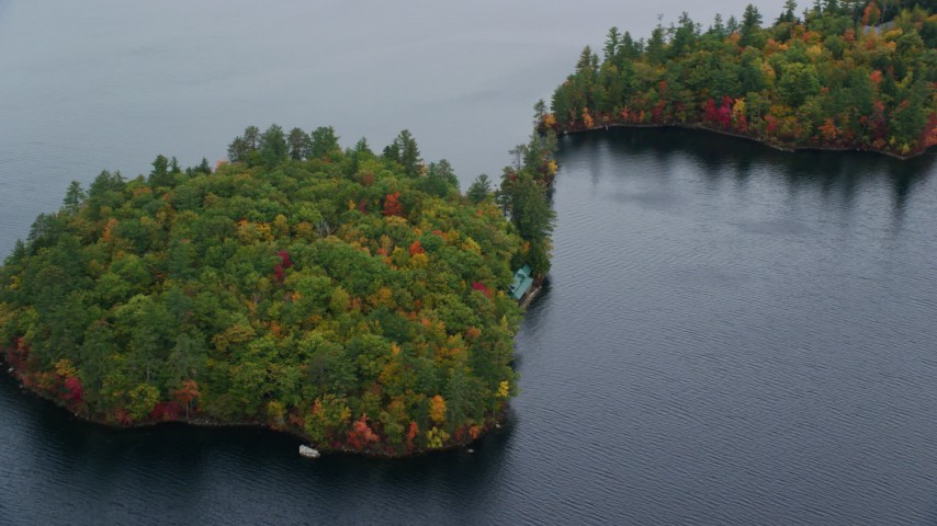 6K aerial video flying by waterfront home on forested Sheep Island, Kezar Lake in autumn, Lovell, Maine Aerial Stock Footage | AX150_140