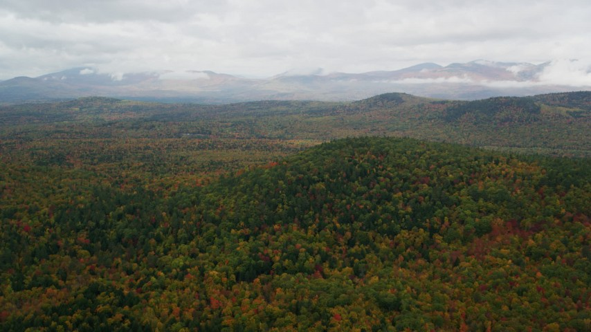 6K aerial video flying over Peaked Hill, colorful forest, approach White Mountains, autumn, Lovell, Maine Aerial Stock Footage | AX150_141