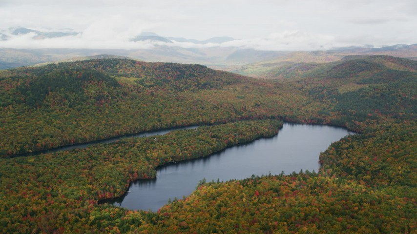 6K stock footage aerial video flying by Horseshoe Pond, dense forest, hills, autumn, overcast, Lovell, Maine Aerial Stock Footage | AX150_143