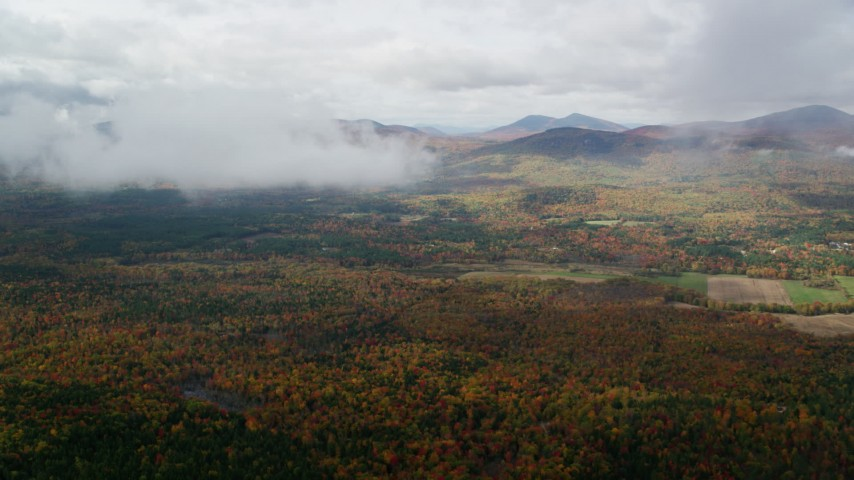 6K stock footage aerial video approaching White Mountains from over forest, autumn, cloudy, Stow, Maine Aerial Stock Footage | AX150_146