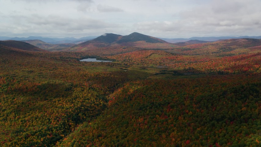 6K stock footage aerial video flying over forest, approaching Mountain Pond, White Mountains, New Hampshire Aerial Stock Footage | AX150_151