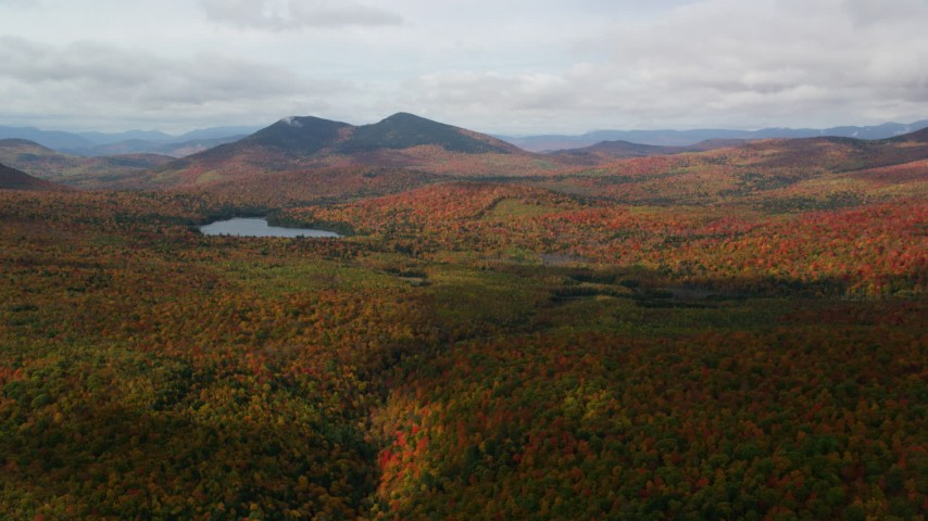 6K aerial video flying over forest, cloudy, autumn, approach Mountain Pond, White Mountains, New Hampshire Aerial Stock Footage | AX150_152