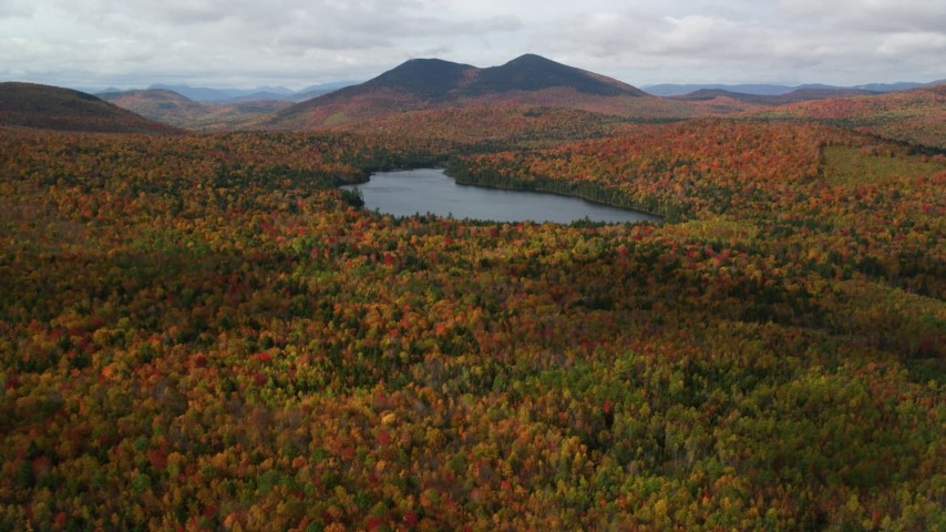 6K stock footage aerial video flying over autumn forest, approach Mountain Pond, White Mountains, New Hampshire Aerial Stock Footage | AX150_153