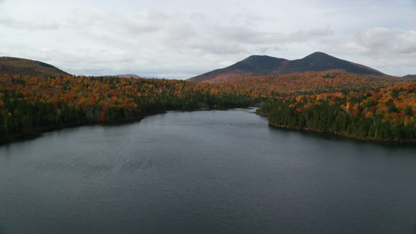 6K stock footage aerial video flying low over Mountain Pond, forest in autumn, approach White Mountains, New Hampshire Aerial Stock Footage | AX150_155