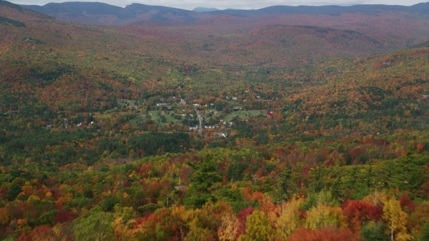 6K stock footage aerial video flying over colorful forest, revealing and approaching Jackson, New Hampshire Aerial Stock Footage | AX150_169
