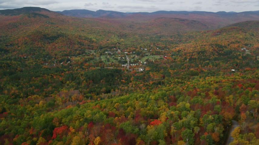 6K stock footage aerial video flying over bright forest, approaching small town of Jackson, New Hampshire Aerial Stock Footage | AX150_170
