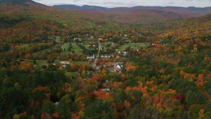 6K stock footage aerial video flying over forest in autumn, approach small town of Jackson, New Hampshire Aerial Stock Footage | AX150_171