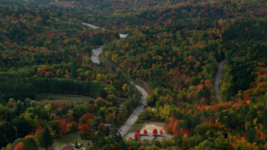 6K stock footage aerial video flying by Route 16, brightly colored forest in autumn, Jackson, New Hampshire Aerial Stock Footage | AX150_182