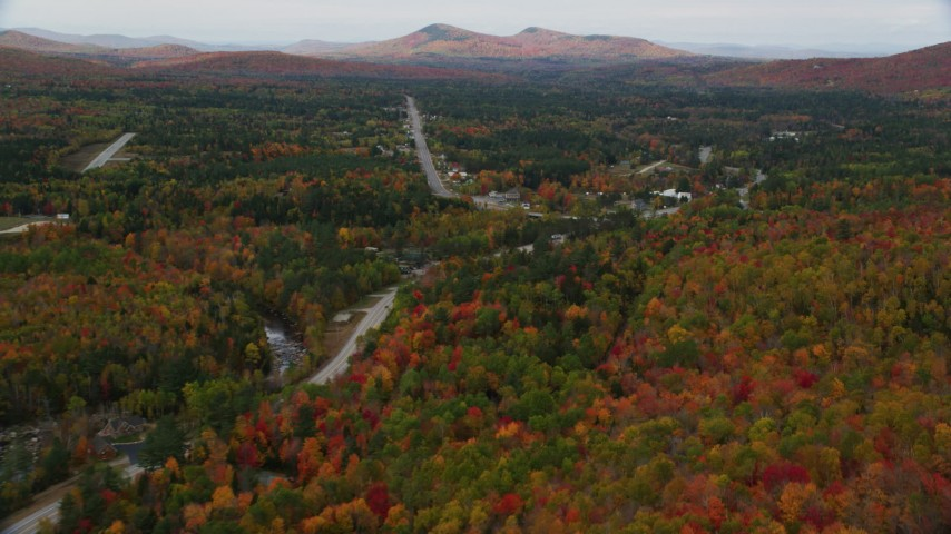 6K stock footage aerial video flying over Highway 302, forest, approach small town, autumn, Carroll, New Hampshire Aerial Stock Footage | AX150_217