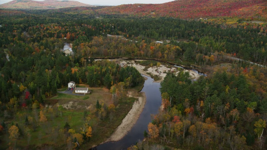 6K stock footage aerial video flying over Ammonoosuc River, approach rural homes, Highway 302, autumn, Carroll, New Hampshire Aerial Stock Footage | AX150_221