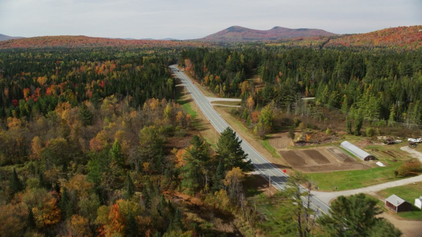 6K stock footage aerial video flying over trees, foliage, approach Highway 302, autumn, Carroll, New Hampshire Aerial Stock Footage | AX150_224