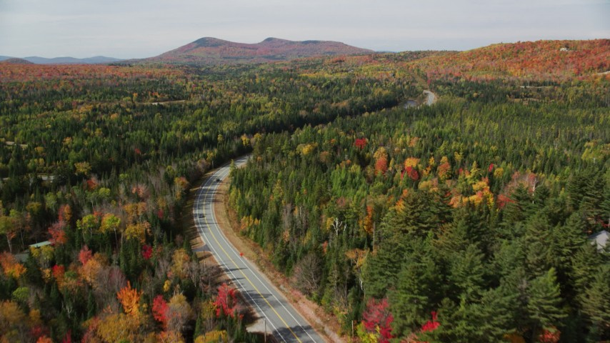 6K stock footage aerial video flying over colorful trees, Highway 302, autumn, Carroll, New Hampshire Aerial Stock Footage | AX150_225