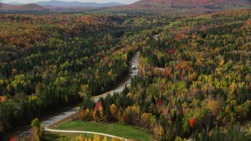6K stock footage aerial video flying over Highway 302 through forest, rural homes, autumn, Carroll, New Hampshire Aerial Stock Footage | AX150_228