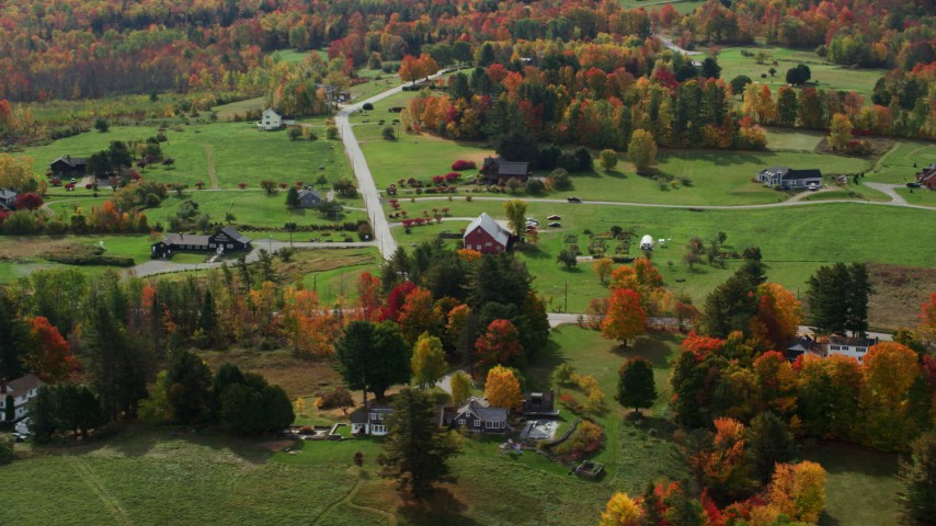 6K stock footage aerial video flying by brightly colored trees, rural homes in autumn, Sugar Hill, New Hampshire Aerial Stock Footage | AX150_245
