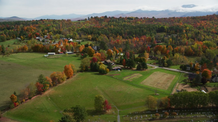 6K stock footage aerial video flying by green fields, colorful trees, small rural town, autumn, Sugar Hill, New Hampshire Aerial Stock Footage | AX150_249