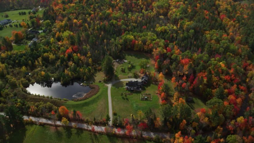 6K stock footage aerial video flying by rural home near pond, brightly colored trees, autumn, Lisbon, New Hampshire Aerial Stock Footage | AX150_258
