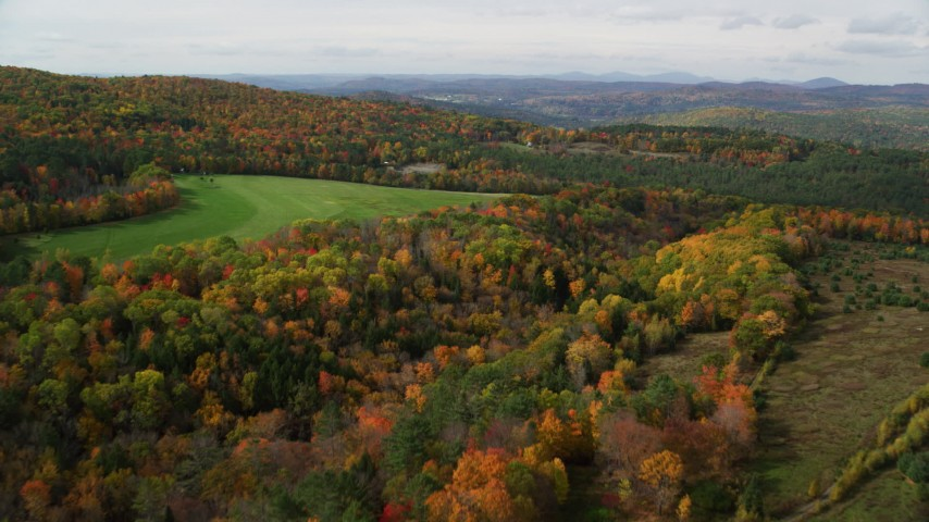 6K stock footage aerial video flying over colorful forest, approach grassy clearing, autumn, Lisbon, New Hampshire Aerial Stock Footage | AX150_263