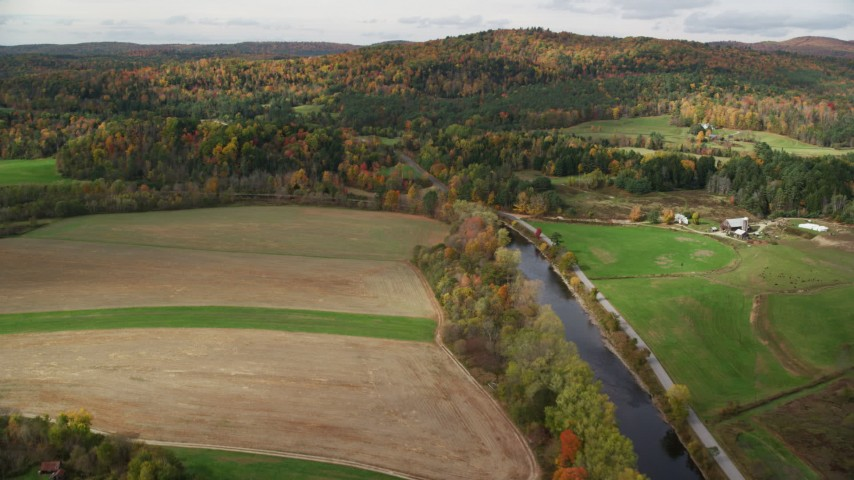 6K stock footage aerial video flying over Ammonoosuc River, by farms, colorful trees, autumn, Lisbon, New Hampshire Aerial Stock Footage | AX150_268