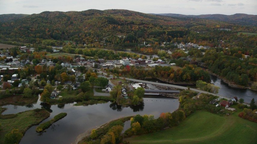6K stock footage aerial video flying over Ammonoosuc River, by rural town, Bath-Haverhill Bridge, autumn, Woodsville, New Hampshire Aerial Stock Footage | AX150_285