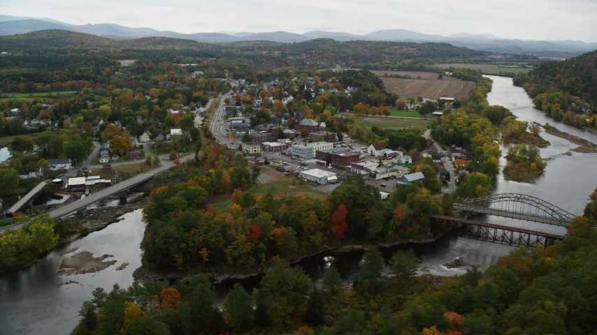 6K stock footage aerial video flying by rural town, bridge, Ammonoosuc River and Connecticut River, autumn, Woodsville, New Hampshire Aerial Stock Footage | AX150_286