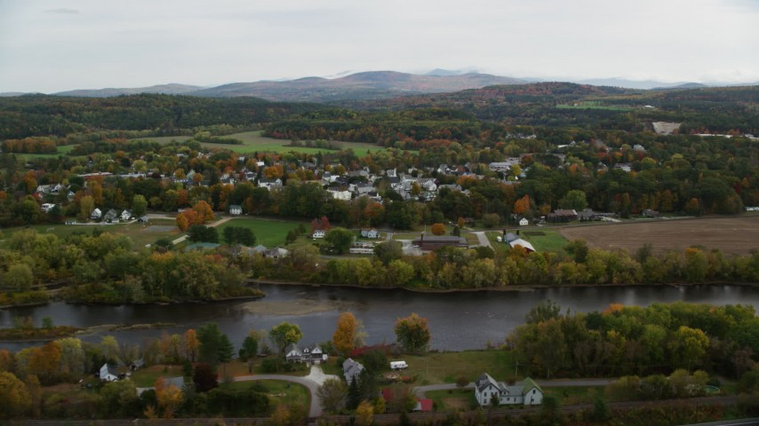 6K stock footage aerial video flying by small rural town, Connecticut River, autumn, overcast, Woodsville, New Hampshire Aerial Stock Footage | AX150_290