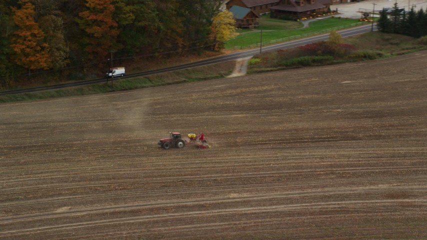 6K stock footage aerial video tracking a tractor on farmland, colorful trees in autumn, Woodsville, New Hampshire Aerial Stock Footage | AX150_291