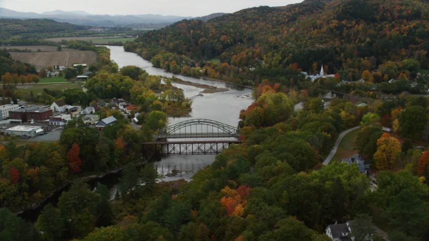 6K stock footage aerial video of small bridges across Connecticut River, small towns autumn, Woodsville, New Hampshire and Wells River, Vermont Aerial Stock Footage | AX150_296