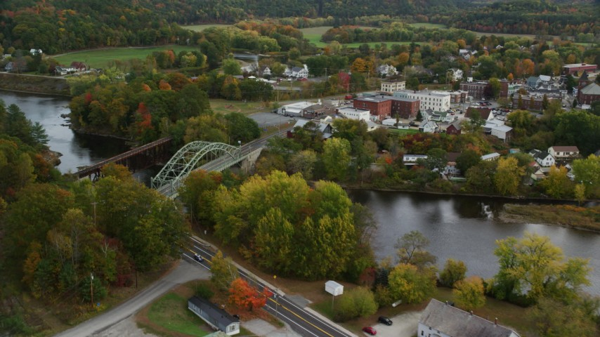 6K stock footage aerial video flying over small rural towns, approach small bridges, Connecticut River, autumn, Wells River, Vermont and Woodsville, New Hampshire Aerial Stock Footage | AX150_300
