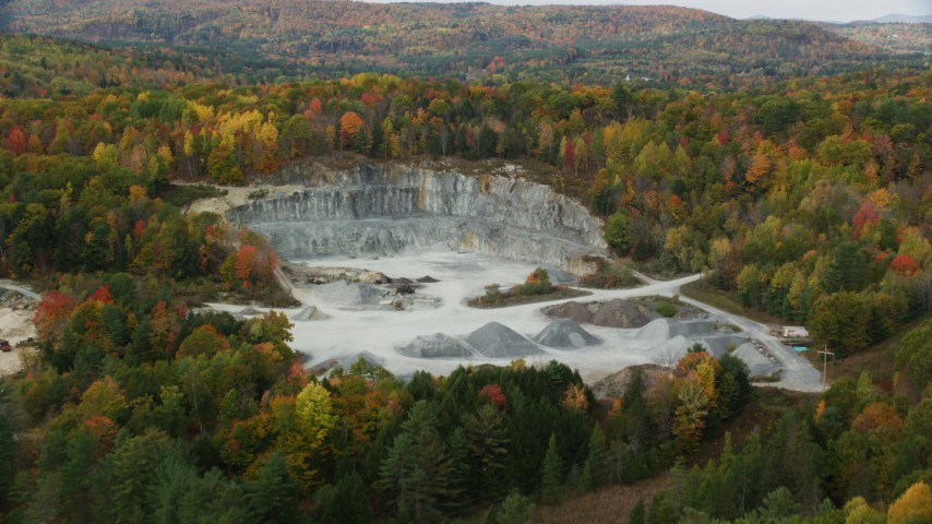 6K stock footage aerial video approaching a small quarry, colorful trees in autumn, tilt down, Wells River, Vermont Aerial Stock Footage | AX150_307