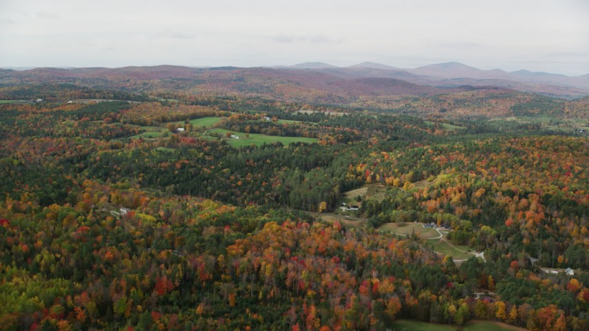 6K stock footage aerial video flying over colorful forest, approaching small farms, autumn, Ryegate, Vermont Aerial Stock Footage AX150_312 | Axiom Images