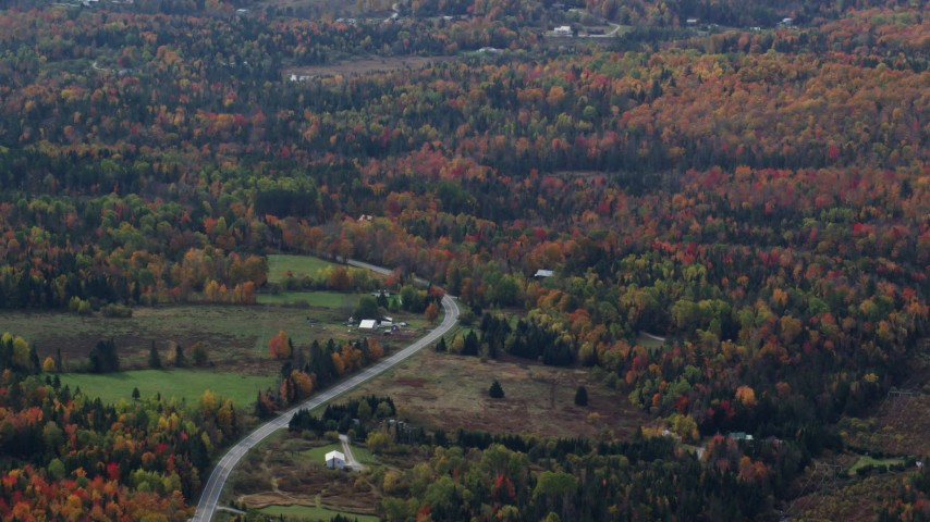 6K stock footage aerial video flying by rural homes, Highway 302 through forest, autumn, overcast, Topsham, Vermont Aerial Stock Footage | AX150_324