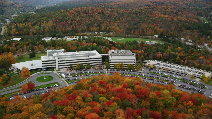 6K stock footage aerial video approaching office buildings, parking lots and tilt down autumn, Montpelier, Vermont Aerial Stock Footage | AX150_364