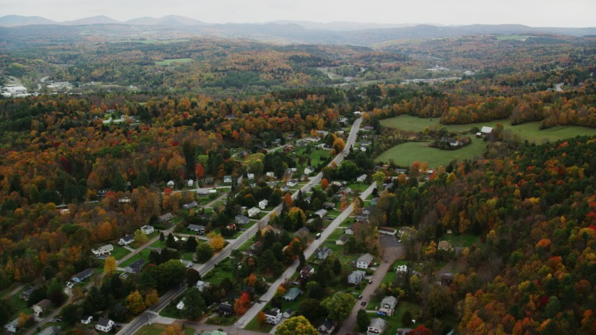 6K stock footage aerial video flying by neighborhood, grassy clearings, colorful foliage, autumn, Montpelier, Vermont Aerial Stock Footage | AX150_393