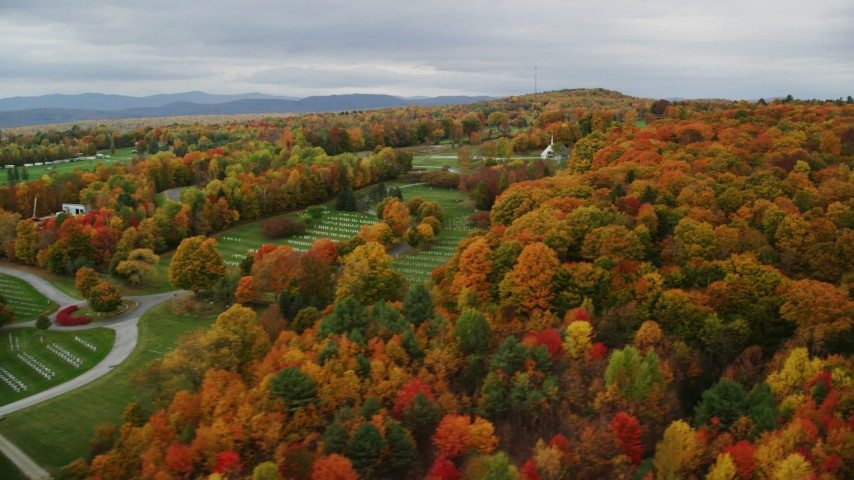 6K stock footage aerial video flying by a cemetery, colorful trees, cloudy sky in autumn, Randolph Center, Vermont Aerial Stock Footage | AX150_406