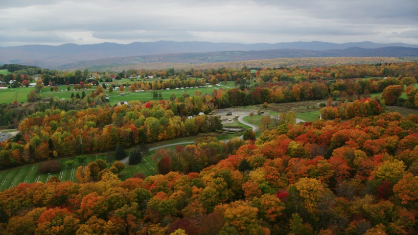 6K stock footage aerial video flying by a cemetery, brightly colored trees, autumn, Randolph Center, Vermont Aerial Stock Footage | AX150_407