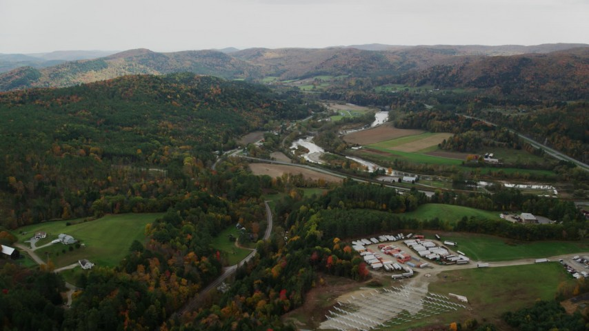 6K stock footage aerial video flying over trailers, approaching White River, Route 107 in autumn, South Royalton, Vermont Aerial Stock Footage | AX150_423